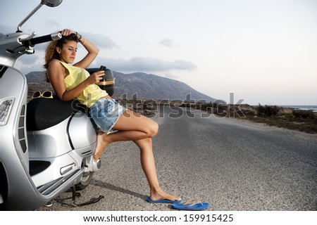 Young female enjoys a motorcycle trip and admires the view while sending messages on her mobile phone - stock photo