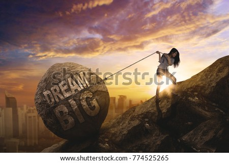 Young female entrepreneur dragging a stone with text of dream big while stepping up on the cliff. Shot at sunset time