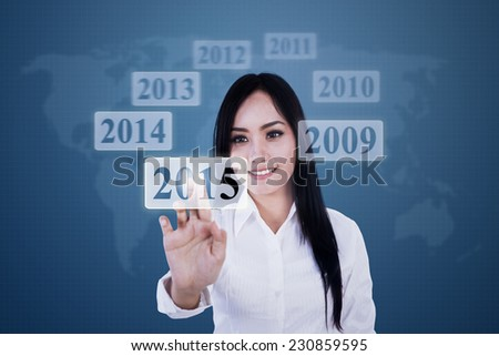 Young female entrepreneur using high tech monitor and pressing a button with number 2015 - stock photo