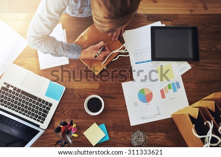 Young female entrepreneur working in a home office at her desk - stock photo