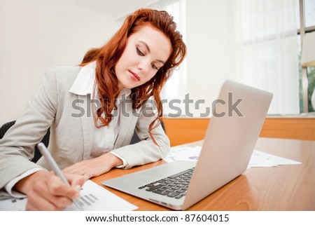 Young female entrepreneur working on her business at the office - stock photo