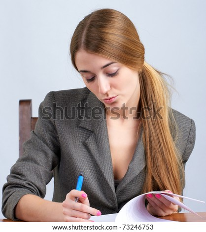 Young female executive reading document - stock photo