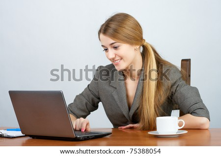 Young female executive working on laptop in the office - stock photo