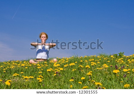young female exercising yoga on flowery meadow