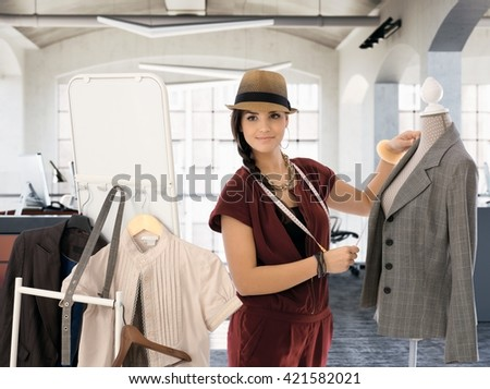Young female fashion designer working in workshop, smiling.
