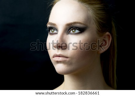 young female fashion girl with blond hair against black background
