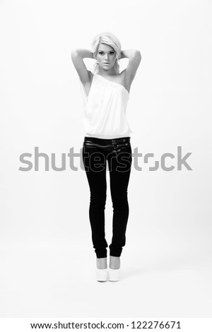 young female fashion model,posing at white background,black and white shot - stock photo