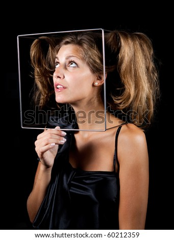 Young female fooling with the cube frame - stock photo