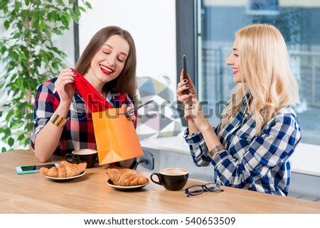 Young female friends dressed casually in checkered shirts looking on the new red scarf sitting at the cafe