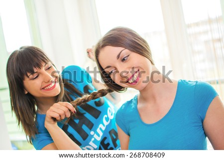 Young female friends having fun at home. One girl smiling while another pulling her long plait. - stock photo