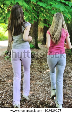 Young female friends running in nature - stock photo