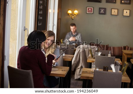 Young female friends using digital tablet with man in background at cafe - stock photo