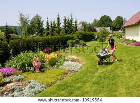young female gardening with a wheelbarrow - stock photo