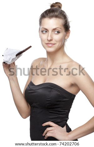 Young female going to bit a chocolate in bars looking aside isolated on white background - stock photo