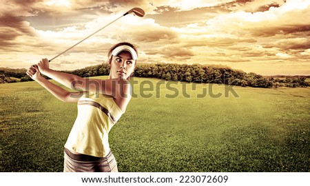 Young female golf player swinging with golf club outdoors. Woman in sportswear playing golf on green field over beautiful landscape background. - stock photo