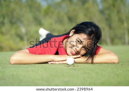 Young, female golf player with ball, at the hole on green