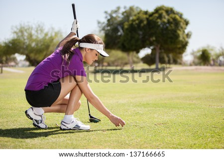 Young female golfer ready for tee off - stock photo
