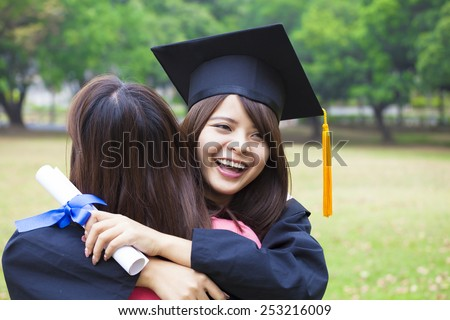 young female graduate hugging her friend at graduation ceremony - stock photo