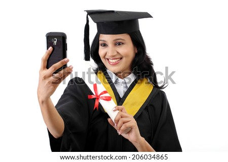 Young female graduated student taking selfie - stock photo