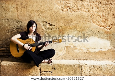 Young female guitar performer posing with her instrument. - stock photo