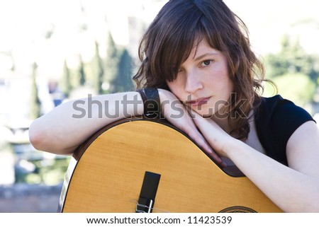 Young female guitar performer staring at camera - stock photo