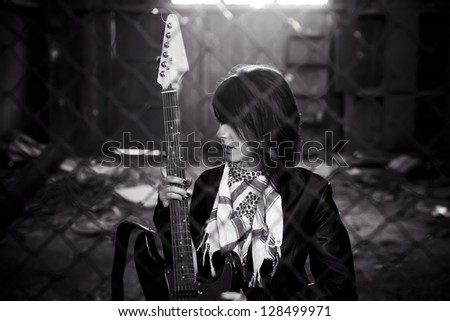 Young female guitarist behind grid fence. - stock photo