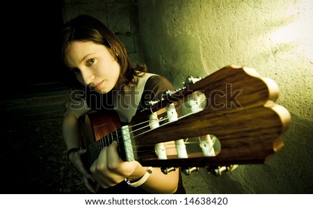 Young female guitarist in the dark - stock photo