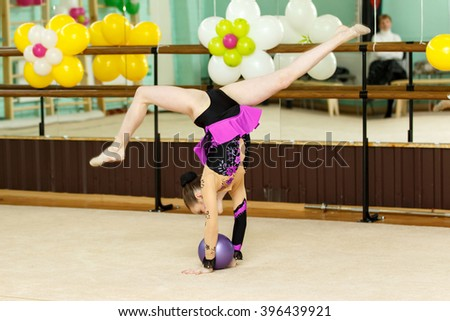 Young female gymnast doing crafty splits on art gymnastics competitions