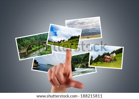 Young female hand touching, pressing digital screen and showing natural art photography or pictures on virtual area. - stock photo