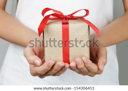 young female hands holding gift, red ribbon - stock photo