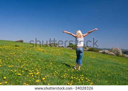 young female having fun on flowery meadow