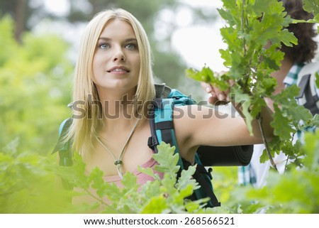Young female hiker in forest with man in background - stock photo
