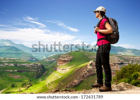 Young female hiking tourist on cliff contemplating open view. - stock photo