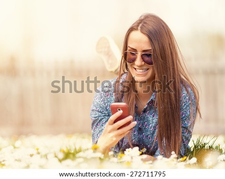 Young female hipster laying on blossom field, in the idyllic nature flourish grassy environment, enjoying the first rays of sun and using your smartphone. Shallow depth of field. Filtered version. - stock photo