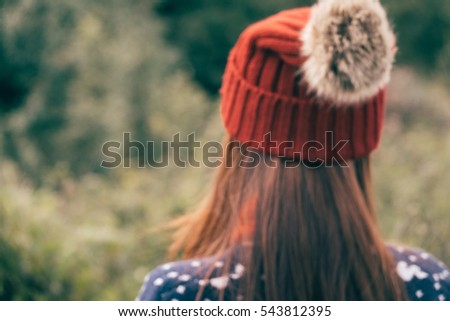 Young female hipster with knitted red hat  traveling along beautiful mountain meadows in the evening background.