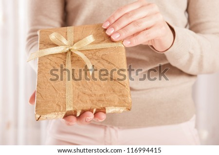 Young female holding a book wrapped in golden paper with ribbon bow