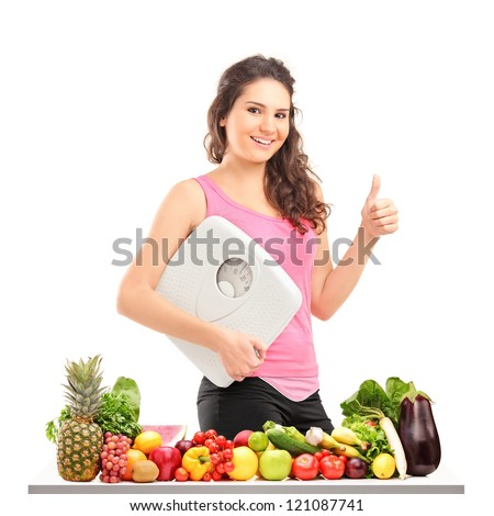 Young female holding a weight scale and giving a thumb up behind a pile of different food isolated on white background