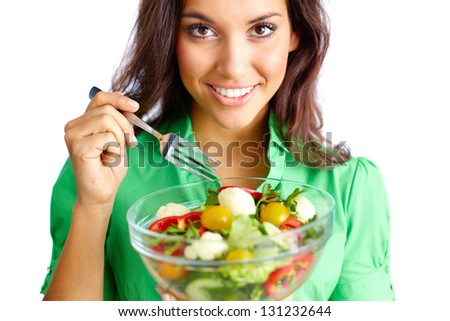 Young female holding bowl with vegetable salad and looking at camera