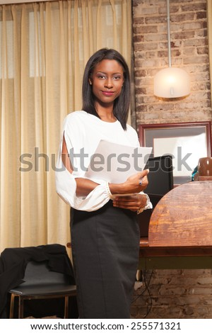 young female holding papers in the office  - stock photo
