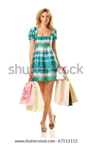 young female holding shopping bags and walking to you isolated on white background