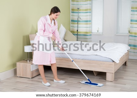 Young Female Housekeeper Cleaning Floor With Mop In Room