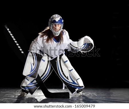 Young female ice hockey goalie in white jersey.