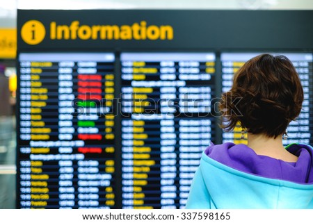 Young female in airport near flight timetable