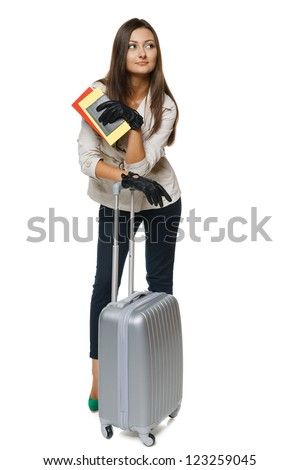 Young female in autumn clothing standing with travel bag, holding passport and tickets,isolated on withe background - stock photo
