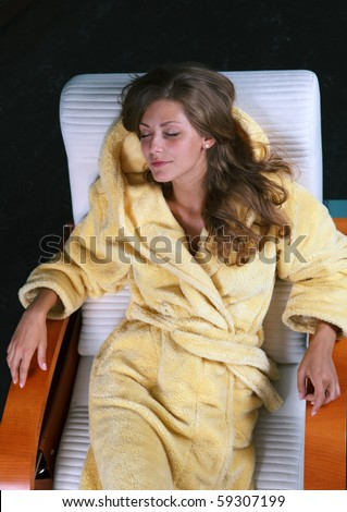 Young female in bathrobe having rest in the chaise longue - stock photo