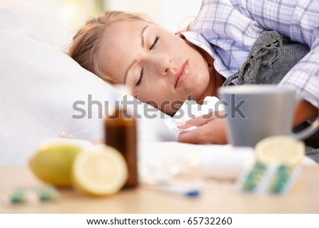 Young female in bed at home caught cold, feeling bad, taking medicines and vitamins, sleeping.? - stock photo