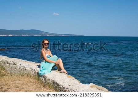 young female in blue dress sitting at the port, near by the blue sea, ocean background