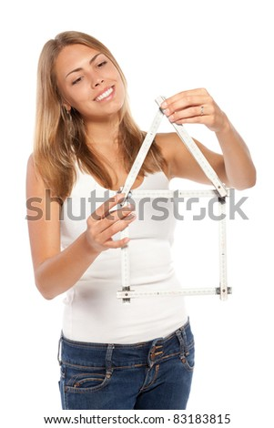 Young female in casual looking at a wooden folding ruler shaped in form of house, over white background - stock photo