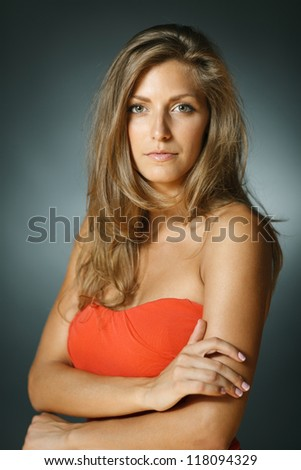 Young female in coral red dress standing with folded hands. Shallow deep of field. - stock photo