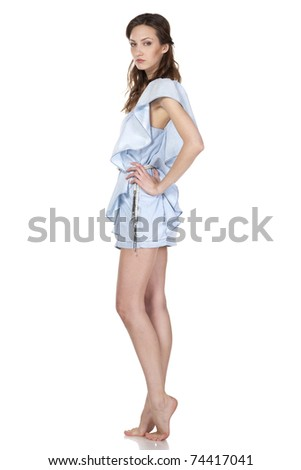 Young female in jeans dress standing with her arms on the waist - stock photo